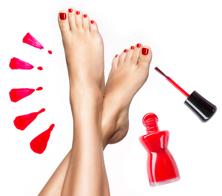 Beautiful female legs with red pedicure and  nail polish  bottle with  brush